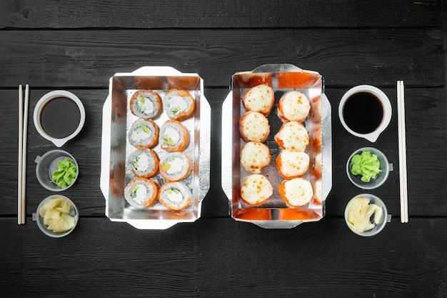 日本食のコンセプト。ケータリング、さまざまな種類の寿司フィラデルフィアロールと焼きエビロールセット、黒い木製のテーブル