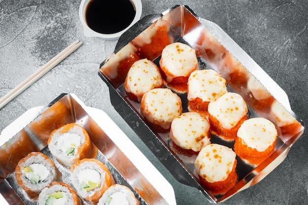 Концепция японской кухни. кейтеринг, различные виды суши-роллов филадельфия и запеченные роллы с креветками, на сером каменном фоне