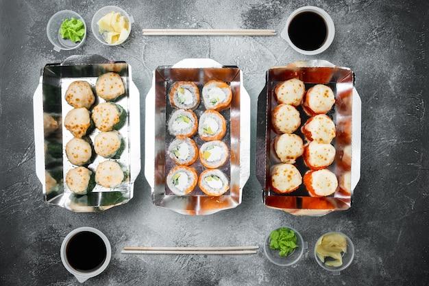 日本食のコンセプト。ケータリング、さまざまな種類の寿司フィラデルフィアロールと焼きエビロールが灰色の石の上にセットされています