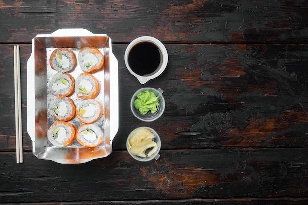 日本食のコンセプト。ケータリング、さまざまな種類の寿司フィラデルフィアロールと焼きエビロールセット、古い暗い木製のテーブル