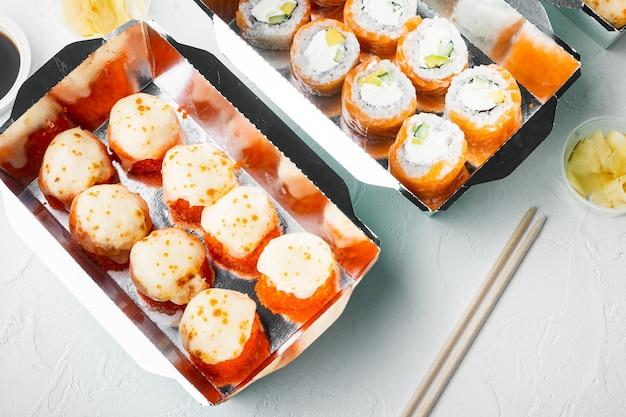 日本食のコンセプト。白い石の上にケータリング、さまざまな種類の寿司フィラデルフィアロールと焼きエビロールがセットされています