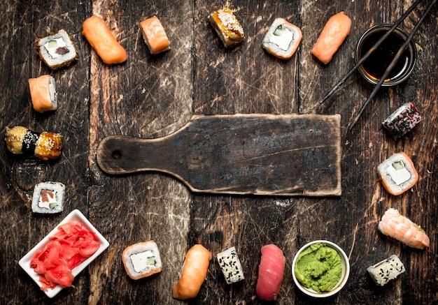 Японская еда. каркас из суши и роллов с соевым соусом, маринованным имбирем и соусом васаби. на старом деревянном столе.