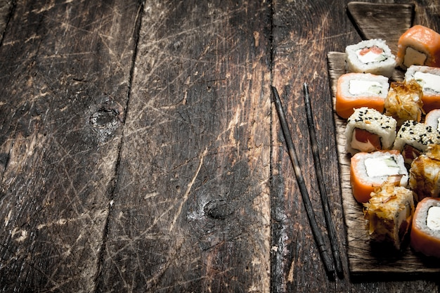 Japanese food. fresh rolls seafood with a chopstick. on the old wooden background.