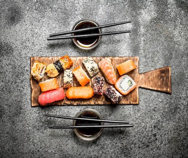 Японская кухня свежие роллы с морепродуктами и соевым соусом на деревенском фоне