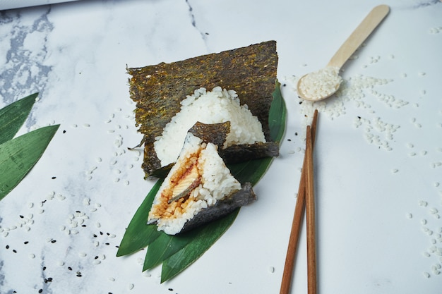 Japanese food made from white rice formed into triangular with eel. copy space