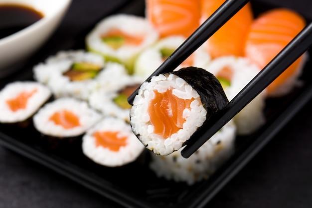 Японская еда: суши маки и нигири на черном фоне, крупный план