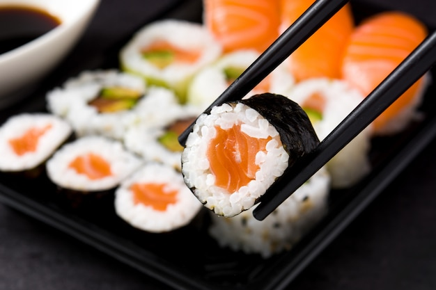 Japanese food: maki and nigiri sushi set on black, close up