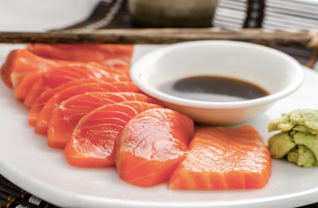Japanese food raw salmon red fish sashimi slices on a dish with sauce