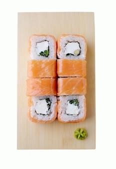 Доставка из ресторана японской кухни, набор суши. суши-роллы с лососем, зеленым луком и сыром, изолированные на деревянной тарелке. вид сверху