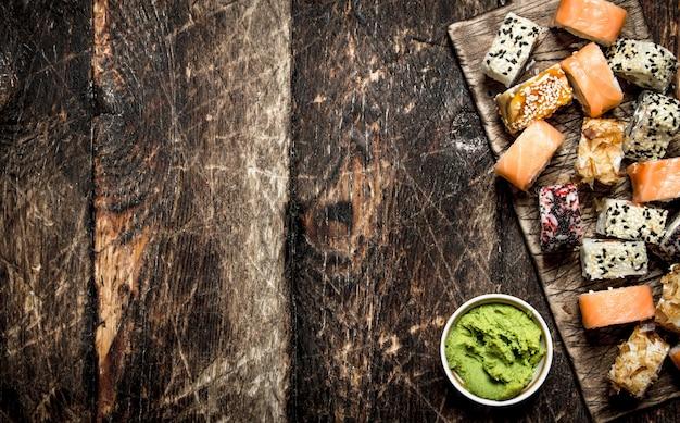 일본 음식. 와사비를 곁들인 신선한 해산물 롤. 오래 된 나무 테이블에.