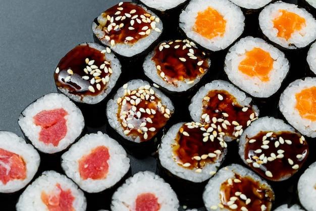 일본 음식. 잘 익은 아보카도, 붉은 생선, 연어, 신선한 쌀과 야채를 김에 곁들인 롤. 롤로 설정