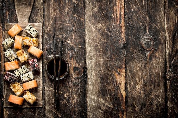 Японская еда. рулетики с соевым соусом. на старом деревянном столе.