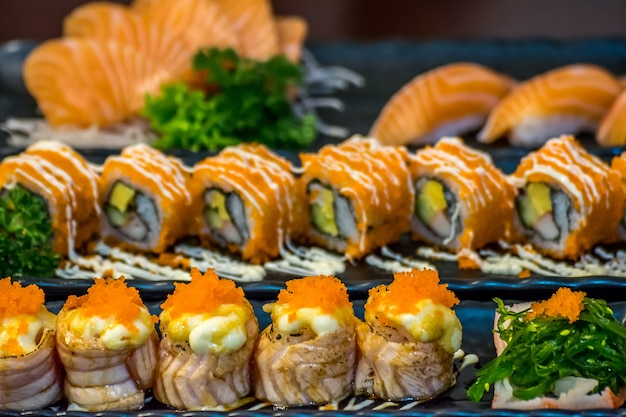 Japanese food in set different types of sushi with seaweed salad and gari (ginger)