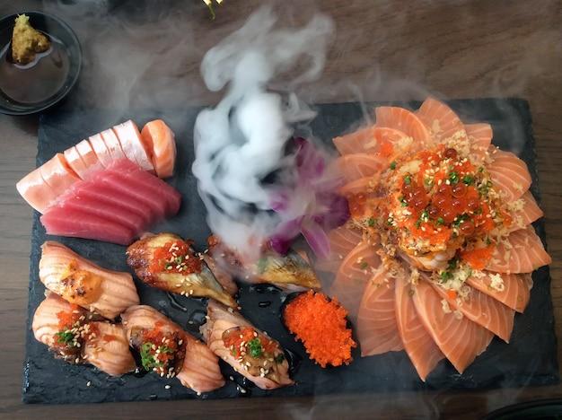 Японская кухня, набор сашими, группа суши с дымом на столе.