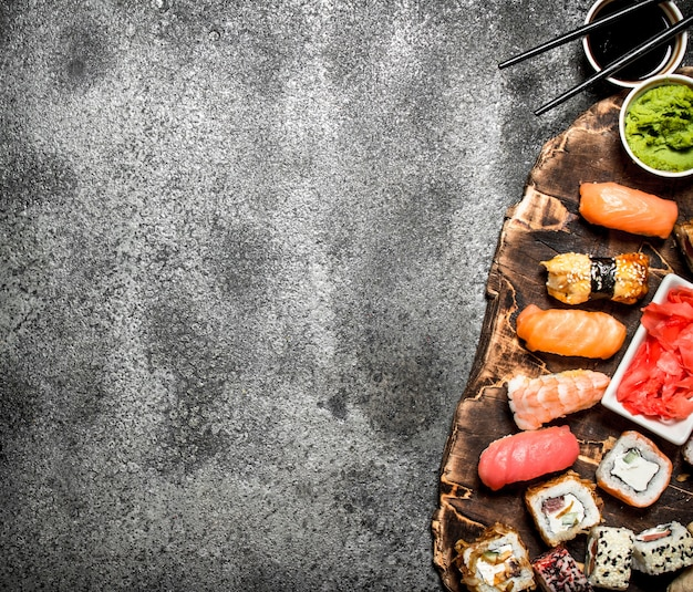 Японская еда. суши и роллы из свежих морепродуктов с соевым соусом и маринованным имбирем. на деревенском столе.