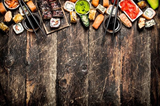 日本食。寿司と新鮮なシーフードを醤油で巻く。古い木の背景に。