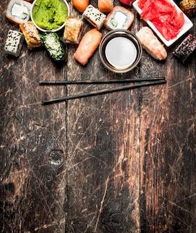 일본 음식. 초밥과 간장을 곁들인 신선한 해산물 롤. 오래 된 나무 테이블에.
