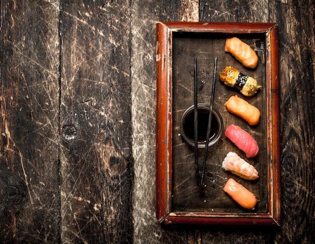 오래 된 나무 배경에 오래 된 쟁반에 간장 일본 음식 스시 신선한 해산물