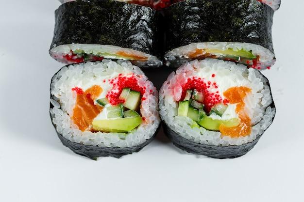 Японская еда суши в листе нори с авокадо, свежей рыбой и красной икрой на белой тарелке