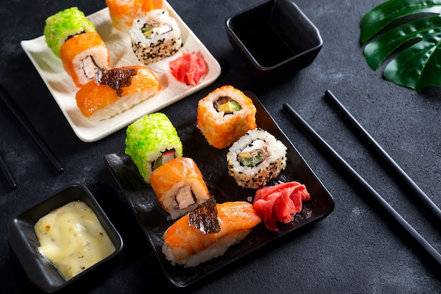 Japanese food- sushi, rolls, chopsticks, soy sauce on black slate background