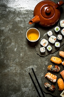 Japanese food sushi rolls and a cup of tea on the stone table