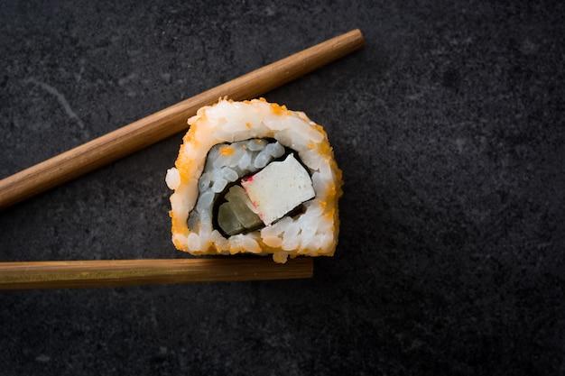 黒いスレート上面に箸で和食寿司をクローズアップ