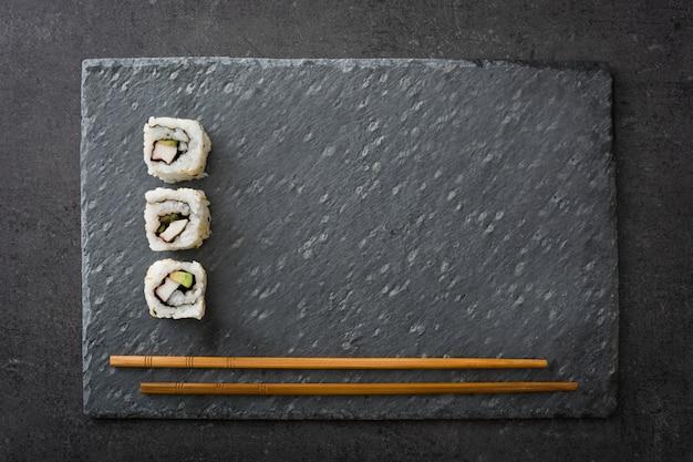 黒いスレートの上面に箸で和食寿司