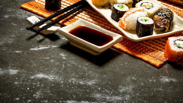 日本食。竹スタンドにロールと醤油を添えた寿司。