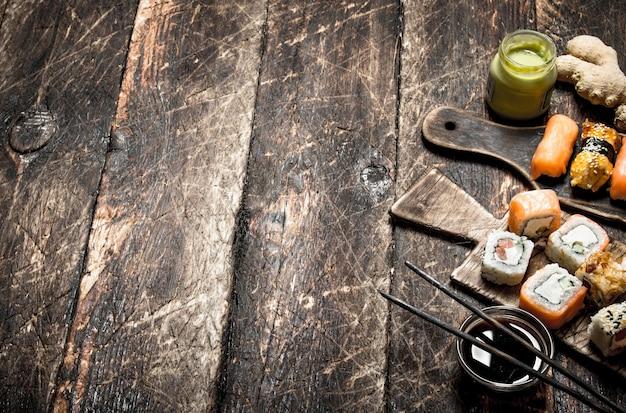 Японская еда. суши-роллы и свежие морепродукты. на старом деревянном столе.
