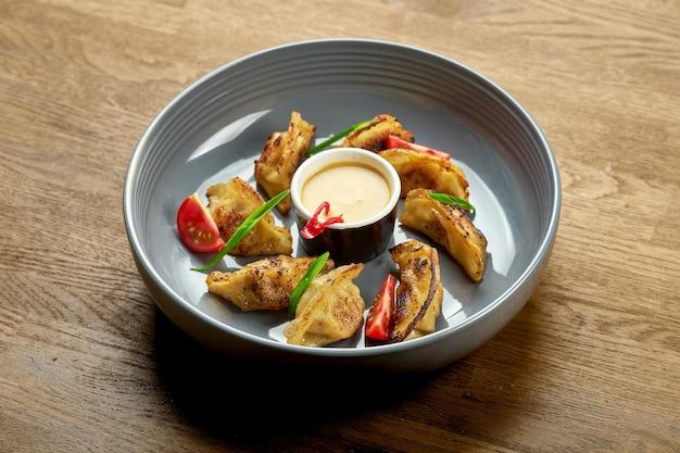 Японская жареная гёза с разными начинками с острым соусом в тарелке на деревянном фоне. крупным планом, выборочный фокус. jiaozi