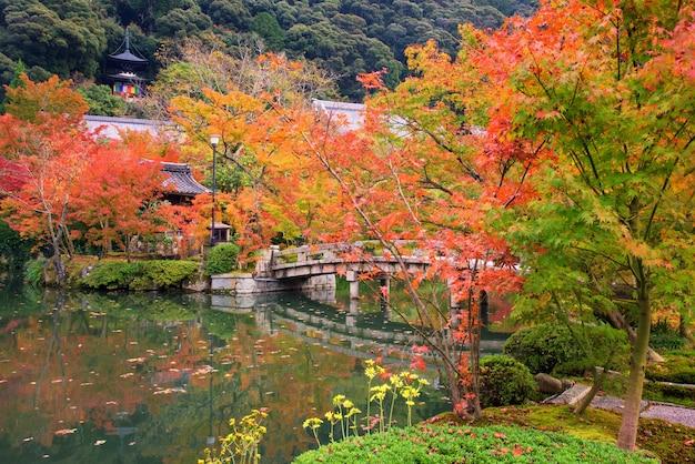 Japanese garden in autumn with stone bridge and shrine at eikando temple, kyoto, japan.