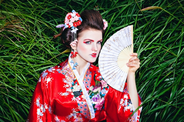 Japanese geisha woman with fancy makeup in garden with a fan