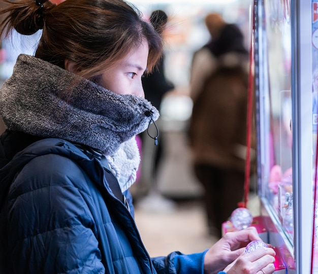 Japanese girl gamer in winter fashion is playing with crane doll machine Premium Photo