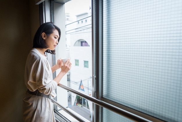 Japanese girl sits at home and drinks tea