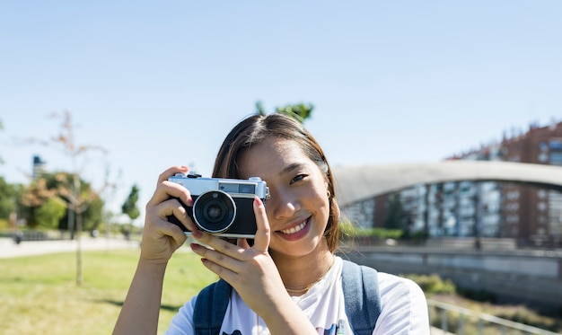 Японская девушка с фотоаппаратом, фон неба, копией пространства