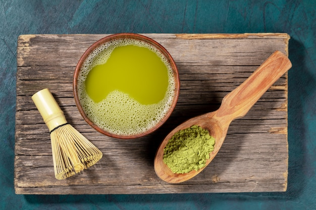 Japanese green matcha tea in wooden cup, matcha powder in wooden spoon and bamboo whisk on old wooden board. top view.
