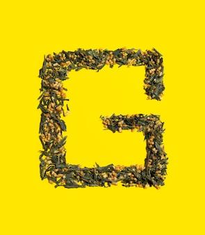 Японский зеленый чай genmaicha. g-образные жареные листья чая из коричневого риса на ярко-желтом фоне с тенью. концепция чая тенденции похудения. натуральный продукт. уход за собой и здоровье