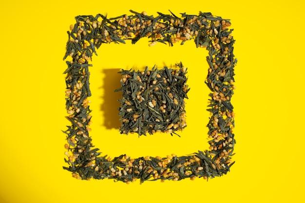 Японский зеленый чай genmaicha. чайные листья с жареным коричневым рисом в форме куба на ярко-желтом фоне с тенью. концепция чая тенденции похудения. натуральный продукт. уход за собой и здоровье