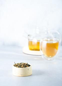 日本の緑茶玄米茶。明るい灰色の背景に影のある玄米炒め茶葉。痩身トレンドティーのコンセプト。紅茶1杯。透明なティーポットを醸造する