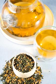 Японский зеленый чай genmaicha. чайные листья с жареным коричневым рисом на ярко-сером фоне с тенью. концепция чая тенденции похудения. чашка чая. заварить прозрачный чайник