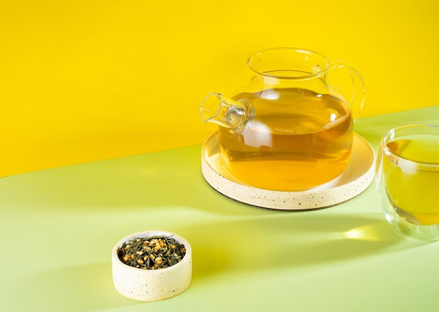 Японский зеленый чай genmaicha. чайные листья с жареным коричневым рисом на ярко-желтом фоне с тенью. концепция чая тенденции похудения. чашка чая. заварить прозрачный чайник