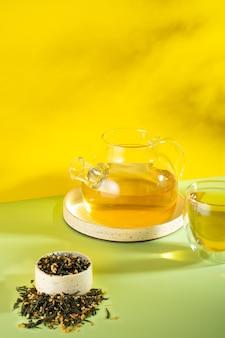 日本の緑茶玄米茶。明るい黄色の背景に影のある玄米炒め茶葉。痩身トレンドティーのコンセプト。紅茶1杯。透明なティーポットを醸造する