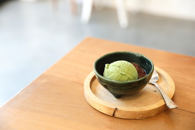 Japanese green tea ice cream with red bean topping on wooden table in coffee shop