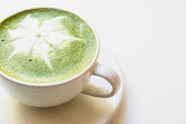 Japanese green tea latte in white cup against white background