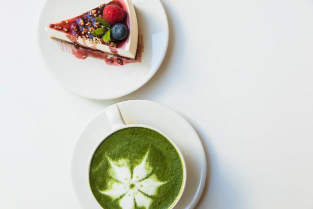 Японский зеленый чай маття в белой чашке и сырный ягодный пирог на тарелке на белом фоне