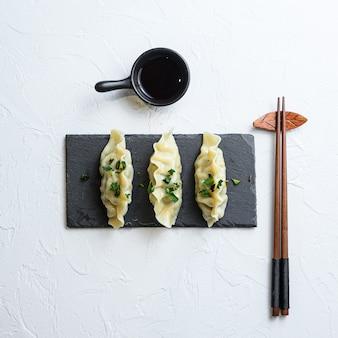 日本の餃子または餃子の醤油とスナック白い背景のアジア料理上面図