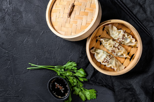 Japanese gyoza in a traditional bamboo steamer. top view. space for text. rustic old vintage black background