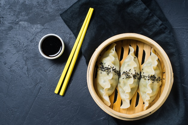 Japanese gyoza in a traditional steamer, yellow chopsticks.
