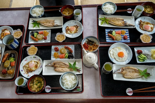 Japanese homestay breakfast including white rice, grilled fish, fried egg, side dishes