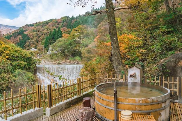 Японские горячие источники онсэн природная ванна в окружении красно-желтых листьев. осенью листья опадают в фукусиме, япония.
